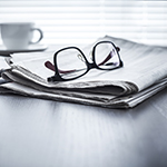 Newspaper with glasses sitting ontop of them