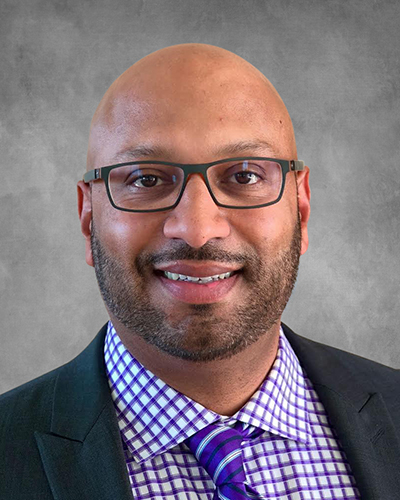 Headshot of Acuity Eye Group co-founder Michael Samuel smiling on a grey background