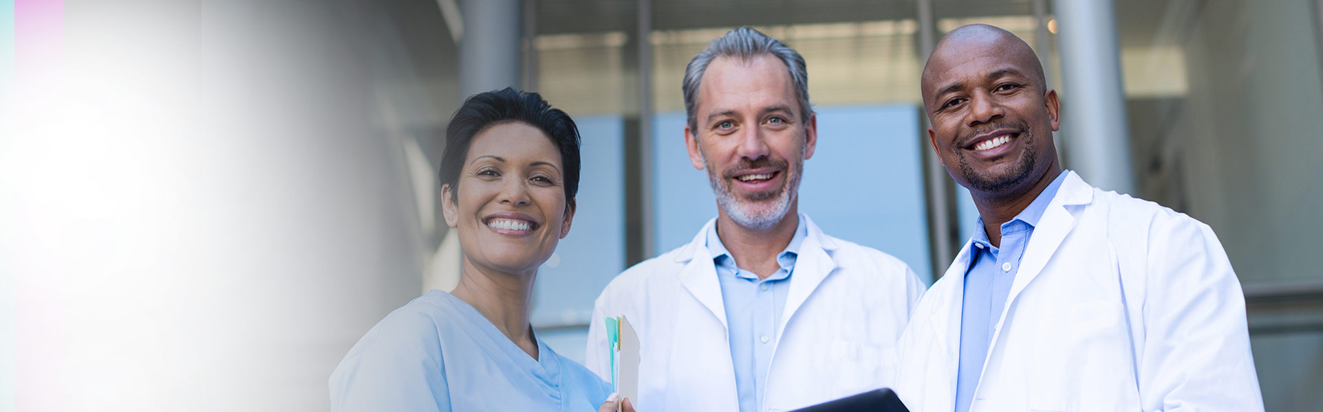 photo of a female doctor and two male doctors smiling outside a medical building