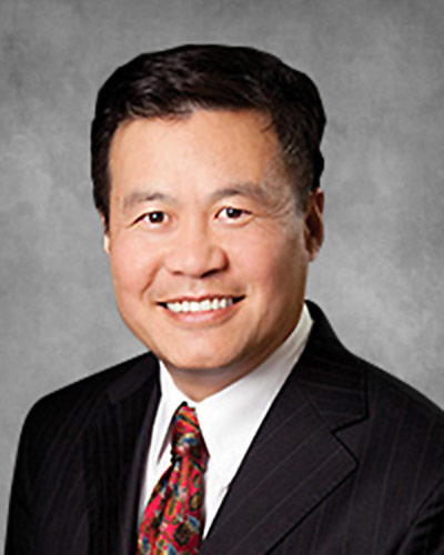 Headshot of Acuity Eye Group co-founder Tom Chang MD smiling on a grey background