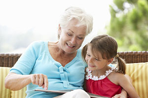 Senior woman reading a book with her young granddaughter