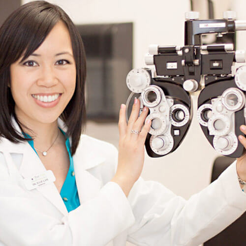 Optometrist smiling with refractor in clinical setting