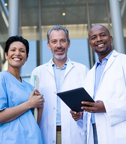 Three medical staff stand together