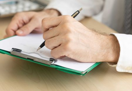 A man holding a pen and writing on a clipboard
