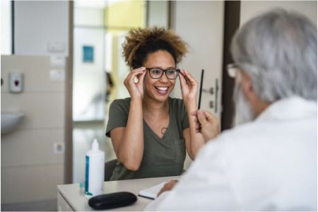 women getting her glasses with the help of an optometrist