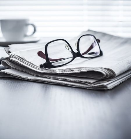 A newspaper with glasses resting on top