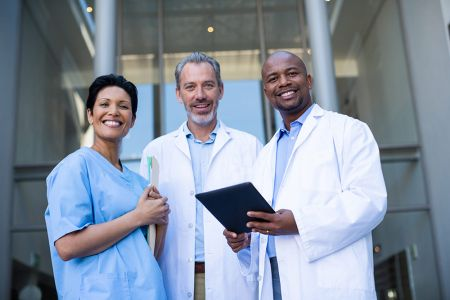 Three professional looking doctors stand and smile at the camera