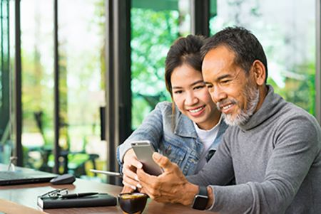 Man smiling at his phone next to his young daughter