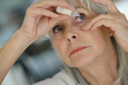 Woman administering eye drops into her own eye