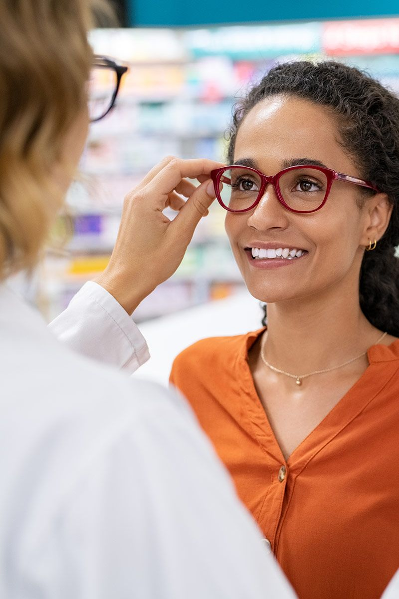 A woman with an orange shirt tries on glasses