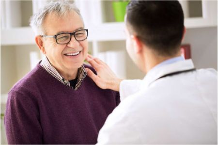 An elderly man in glasses is reassured by a doctor